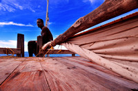 A young man sitting on top of a wooden boat looking at the horizon in Zanzibar Island photo for sale