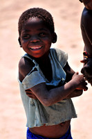 Young African Girl wearing old dirty cloth smiling to the camera in Namibia